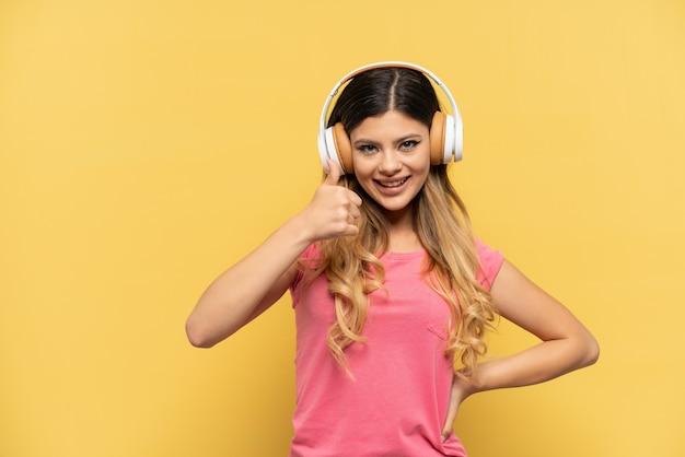 Jeune fille russe isolée sur fond jaune, écoutant de la musique et avec le pouce vers le haut