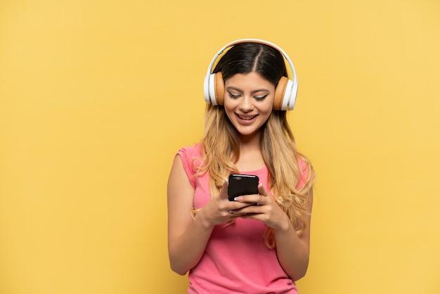 Jeune fille russe isolée sur fond jaune, écoutant de la musique et regardant vers un mobile