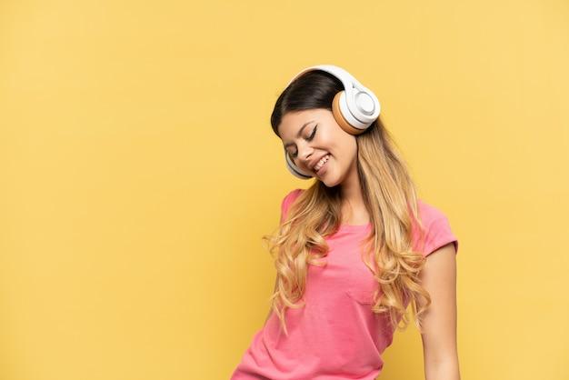 Jeune fille russe isolée sur fond jaune, écouter de la musique