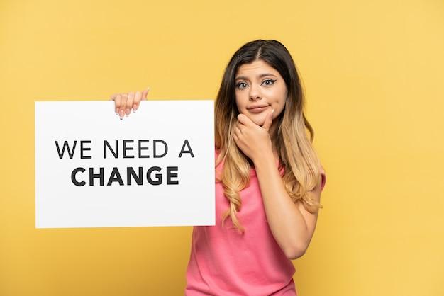 Jeune fille russe isolée sur fond jaune tenant une pancarte avec du texte nous avons besoin d'un changement et de la pensée