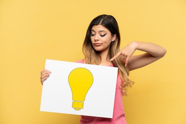 Jeune fille russe isolée sur fond jaune tenant une pancarte avec l'icône de l'ampoule et la pointant