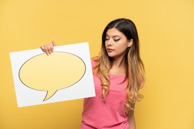 Jeune fille russe isolée sur fond jaune tenant une pancarte avec l'icône bulle