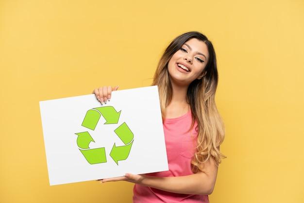 Jeune fille russe isolée sur fond jaune tenant une pancarte avec icône de recyclage avec une expression heureuse