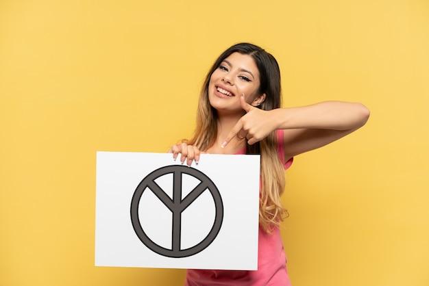 Jeune fille russe isolée sur fond jaune tenant une pancarte avec le symbole de la paix et le pointant