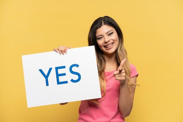 Jeune fille russe isolée sur fond jaune tenant une pancarte avec le texte oui et le pointant
