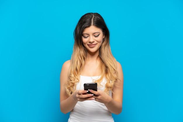 Jeune fille russe isolée sur mur bleu envoyant un message avec le mobile