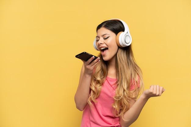 Jeune fille russe isolée sur un mur jaune, écoutant de la musique avec un mobile et chantant
