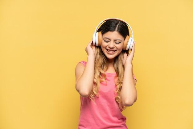 Jeune fille russe isolée sur mur jaune, écouter de la musique