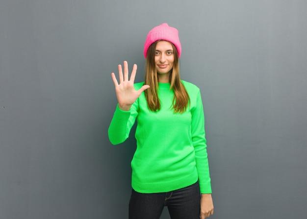 Jeune fille russe naturelle montrant le numéro cinq