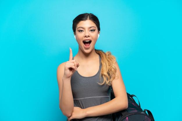 Jeune fille russe de sport avec sac de sport isolé sur fond bleu pensant à une idée pointant le doigt vers le haut