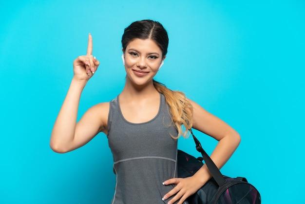 Jeune fille russe de sport avec sac de sport isolé sur fond bleu pointant vers une excellente idée