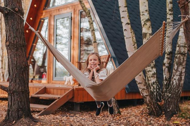 Jeune fille s'amusant dans un hamac sur une chaude journée d'automne