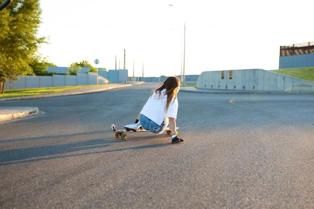 Jeune fille s'amuser avec la planche à roulettes sur la route. jeune femme patinant par une journée ensoleillée
