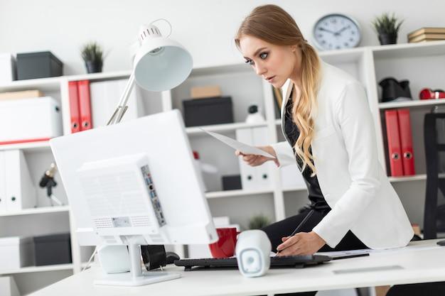 La jeune fille s'assit sur le bureau du bureau et travailla avec un ordinateur et des documents.