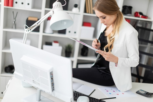 La jeune fille s'assit sur le bureau du bureau et travailla avec un ordinateur et des documents