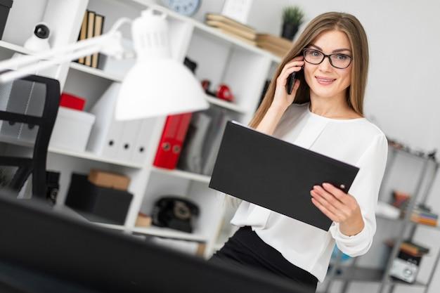 La jeune fille s'assit sur la table dans le bureau, tenant une tablette avec des draps à la main et parlant au téléphone.