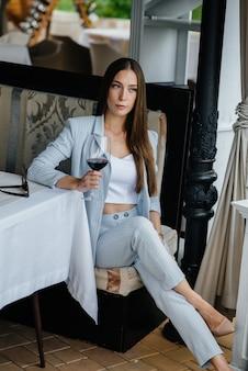 Jeune fille s'assoit et boit du vin sur la véranda d'une maison. vacances.