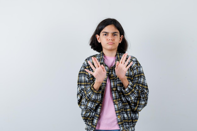 Jeune fille s'étirant les mains pour s'arrêter en chemise à carreaux et t-shirt rose et l'air sérieux. vue de face.