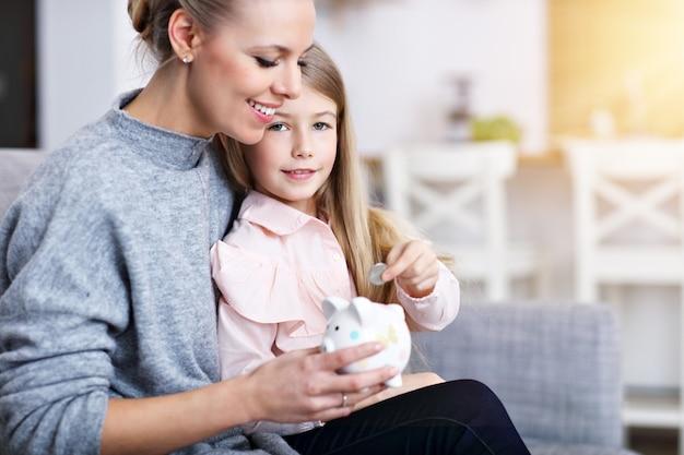Jeune fille et sa mère avec tirelire assis à table