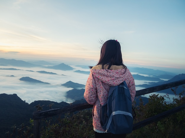 Jeune fille avec sac à dos, appréciant le lever du soleil sur le sommet de la montagne.
