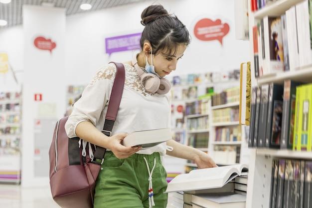 Une jeune fille avec un sac à dos et des écouteurs sélectionne un livre sur les étagères du magasin.