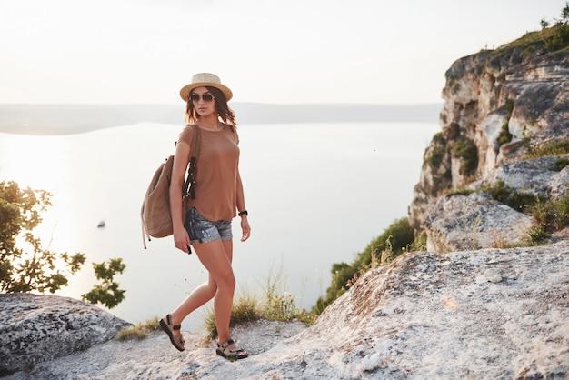 Jeune fille avec sac à dos, profitant du coucher de soleil au sommet de la montagne rocheuse concept de vacances aventure voyage lifestyle