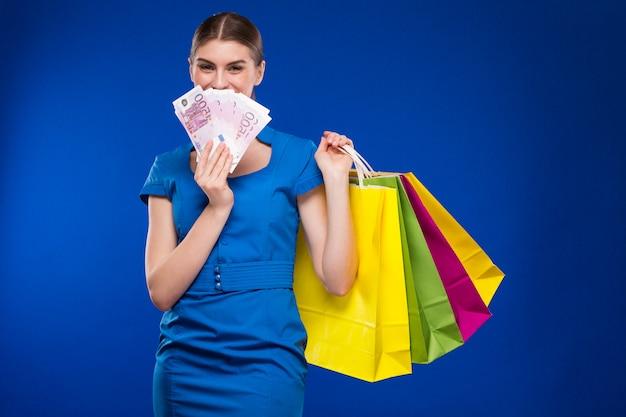 Jeune fille avec des sacs et beaucoup d'argent entre les mains de