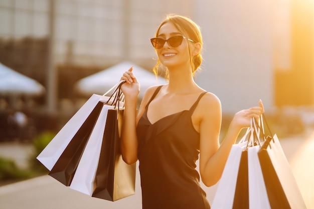 Jeune fille avec des sacs colorés se promenant dans la ville après le shopping.