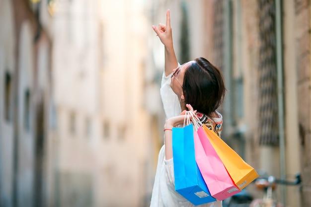 Jeune fille avec des sacs de shopping dans une rue étroite en europe. portrait d'une belle femme heureuse tenant des sacs shopping souriant