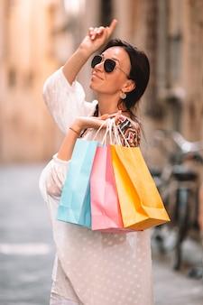 Jeune fille avec des sacs de shopping dans une rue étroite en europe.