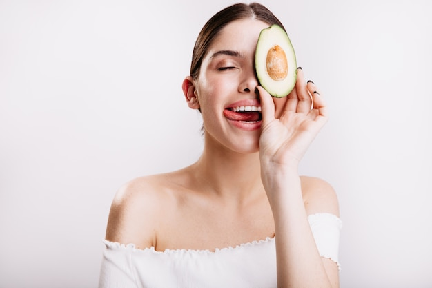 Jeune fille sans maquillage en haut blanc lèche ses lèvres, posant avec un avocat savoureux et sain sur un mur isolé.