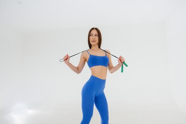 Jeune fille sautant à la corde dans un survêtement bleu sur fond blanc. fitness, mode de vie sain.
