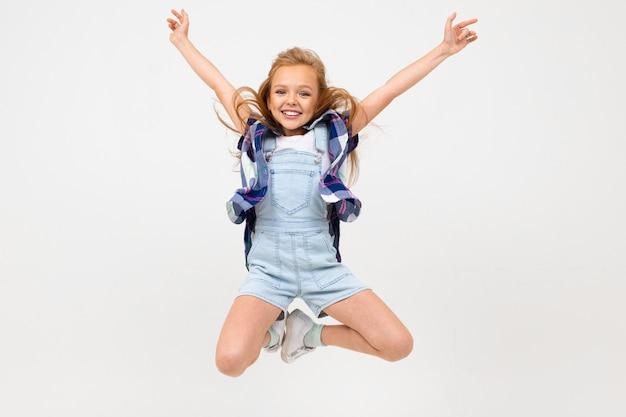 Jeune fille sautant dans des vêtements décontractés sur un fond de studio bleu clair