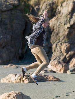 Jeune fille sautant sur la plage, twillingate, north twillingate island, terre-neuve-et-labrador, canada