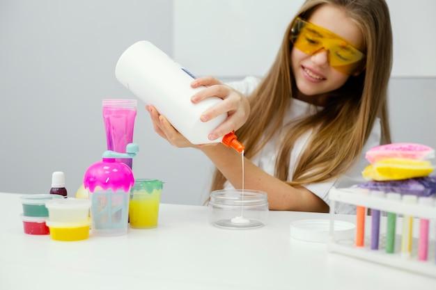 Jeune fille scientifique faisant de la boue dans le laboratoire