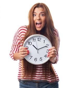 Jeune fille se cachant derrière une horloge.