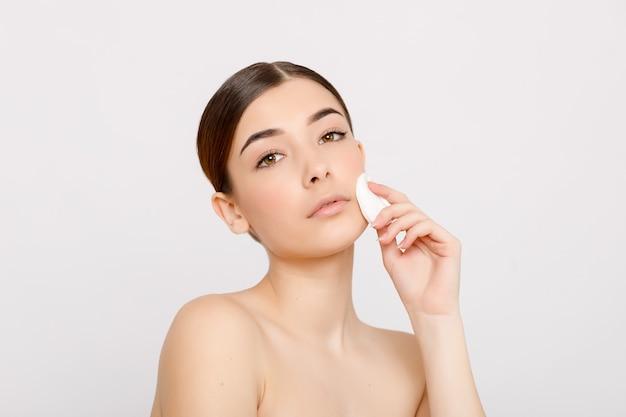 Jeune fille se démaquiller le visage avec un coton