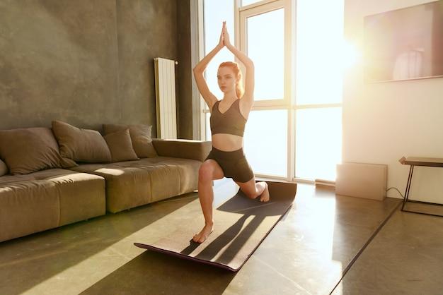 Jeune fille se détendre en position de yoga devant une fenêtre lumineuse