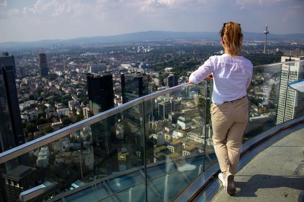 La jeune fille se dresse sur une haute tour dans la ville de frankfurn on main et regarde la ville