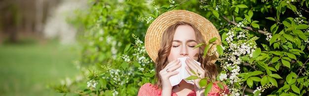 Jeune fille se moucher et éternuer dans les tissus devant l'arbre en fleurs. allergènes saisonniers affectant les personnes. belle dame a une rhinite.