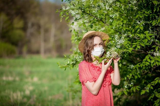 Jeune fille se moucher et éternuer dans les tissus en face de l'arbre en fleurs