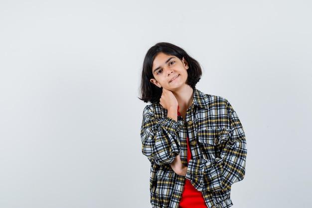 Jeune Fille Se Penchant Le Cou Sur La Paume En Chemise à Carreaux Et T-shirt Rouge Et L'air Mignon. Vue De Face. Photo gratuit