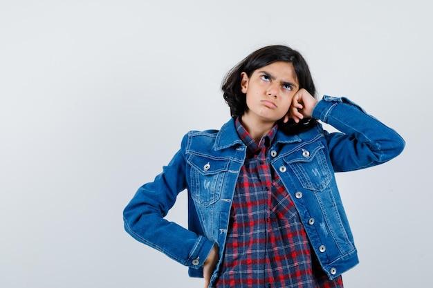 Jeune fille se penchant la joue sur la main tout en tenant la main sur la taille en chemise à carreaux et veste en jean et l'air pensif. vue de face.