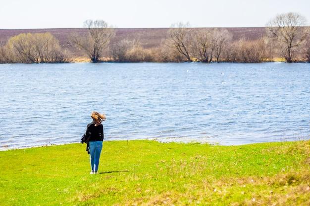 Jeune fille se promène au bord de la rivière. mode de vie sain. zone écologiquement propre