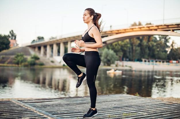 Jeune fille se réchauffant sur une plate-forme en bois sur la rive