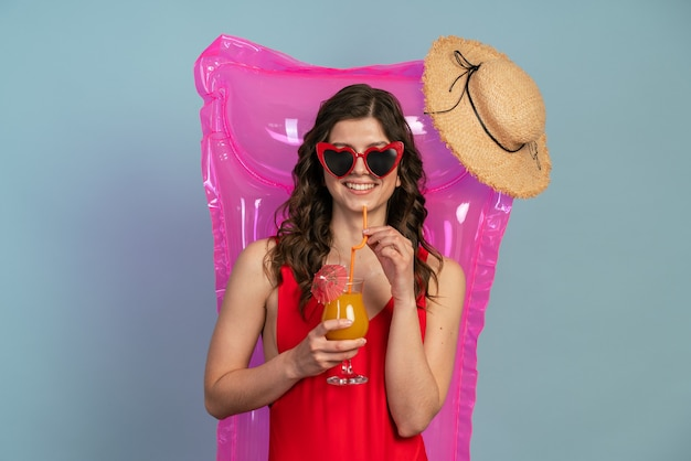 La jeune fille se repose sur un matelas pneumatique, tenant un cocktail dans ses mains