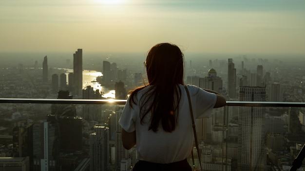 Jeune fille se tenait sur le toit du bâtiment en regardant la ville pleine de poussière et de pollution de l'air