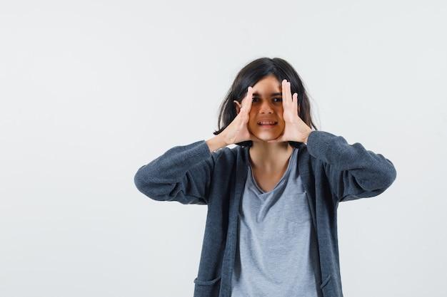 Jeune fille se tenant la main près du visage, essayant d'appeler quelqu'un en t-shirt gris clair et sweat à capuche zippé gris foncé et à la recherche de mignon.