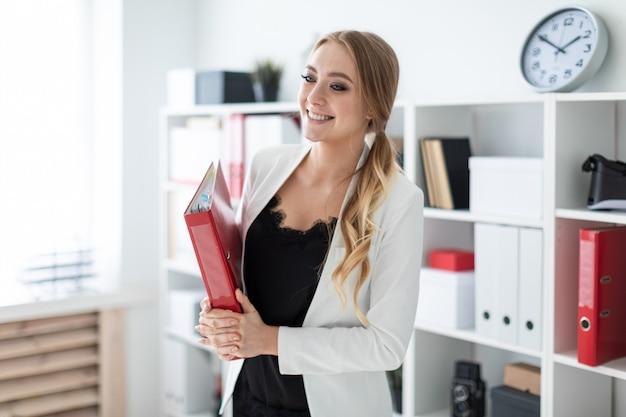 Une jeune fille se tient dans le bureau à côté de l'étagère et tient un dossier avec des documents dans ses mains.