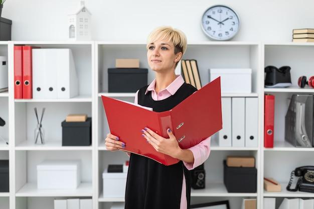 Une jeune fille se tient dans le bureau avec un dossier rouge dans ses mains.